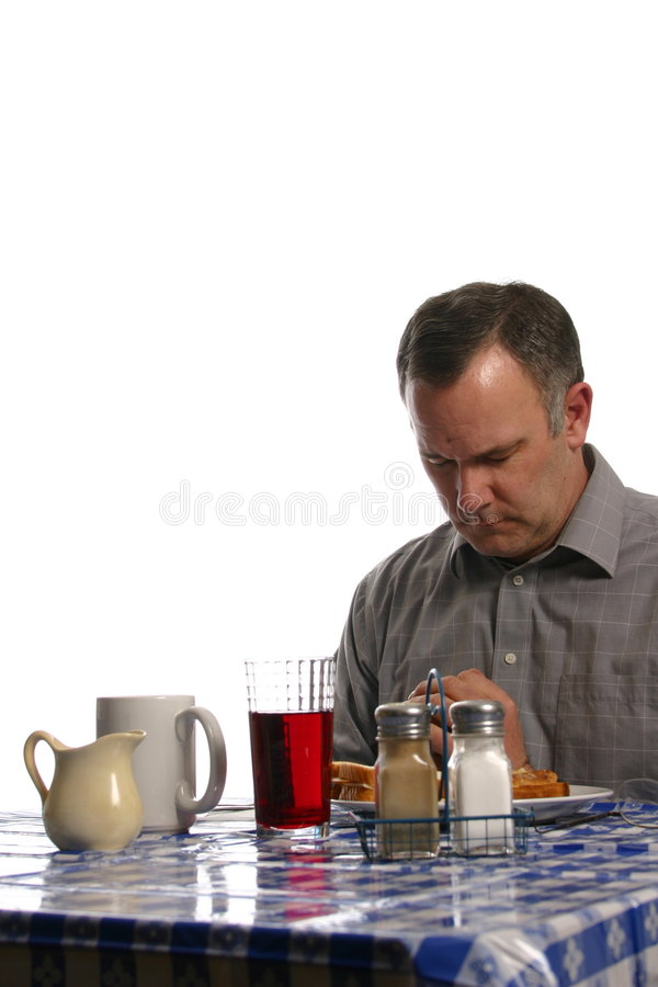 Man praying before meal in diner. Middle-aged man saying grace at a table in a diner isolated on white space stock photos