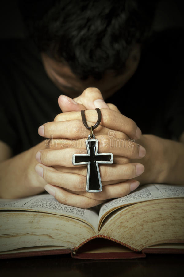 Man praying to God. With bible and rosary on his hands stock photography