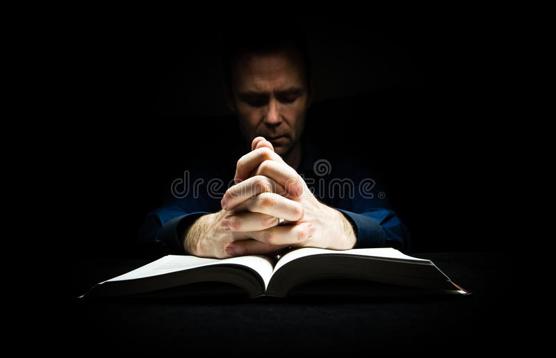 Man praying to God. With his hands resting on a bible royalty free stock photos