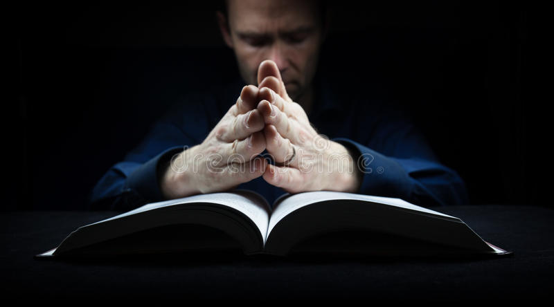 Man praying to God. With his hands resting on a bible royalty free stock photography