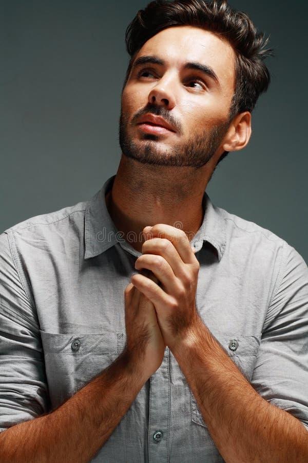 Man prays. A young man prays over studio grey background stock photos