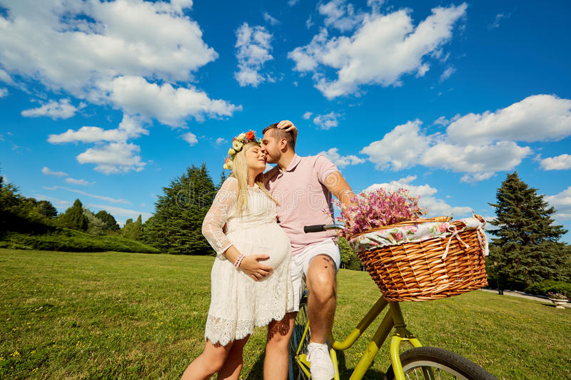 Man and a pregnant woman happy nature in park .Young happy family. Pregnant couple embracing and kissing on the background of blu stock photo