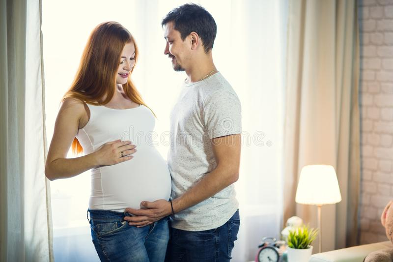 Man and a pregnant young woman are waiting for a child at home b. Man and a pregnant young women are waiting for a child at home by the window. Loving family royalty free stock image