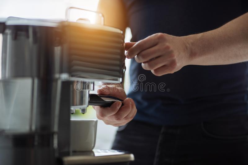 A man prepares espresso for a coffee maker royalty free stock photography