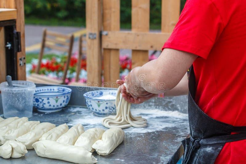 Man prepares noodles in a street cafe. Ramen. Fresh dough on the table. China, Korea, Japan, Vietnam, Thailand.  East Asian selective focus stock photos