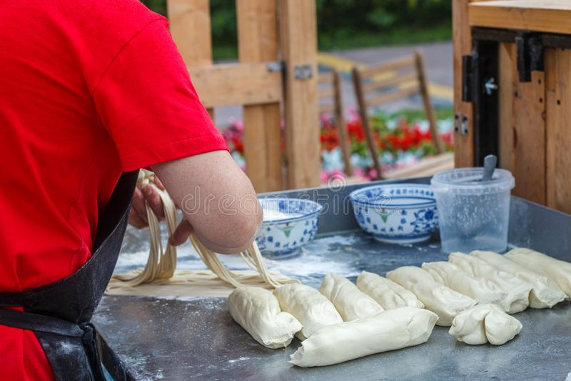 Man prepares noodles in a street cafe. Ramen. Fresh dough on the table. China, Korea, Japan, Vietnam, Thailand.  East Asian selective focus royalty free stock photography