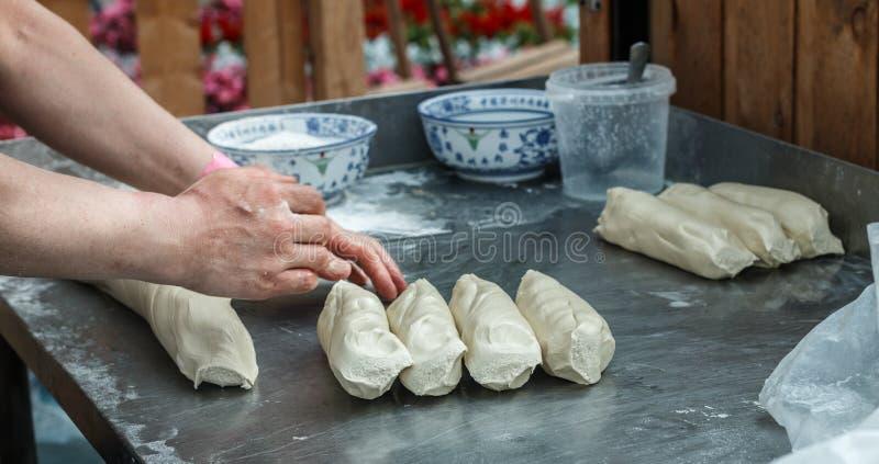 Man prepares noodles in a street cafe. Ramen. Fresh dough on the table. China, Korea, Japan, Vietnam, Thailand.  East Asian selective focus stock photo
