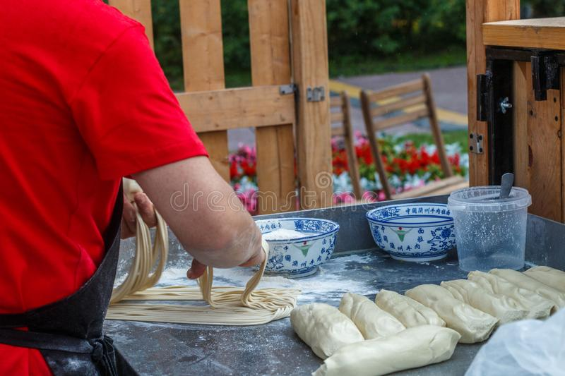 Man prepares noodles in a street cafe. Ramen. Fresh dough on the table. China, Korea, Japan, Vietnam, Thailand.  East Asian selective focus royalty free stock images