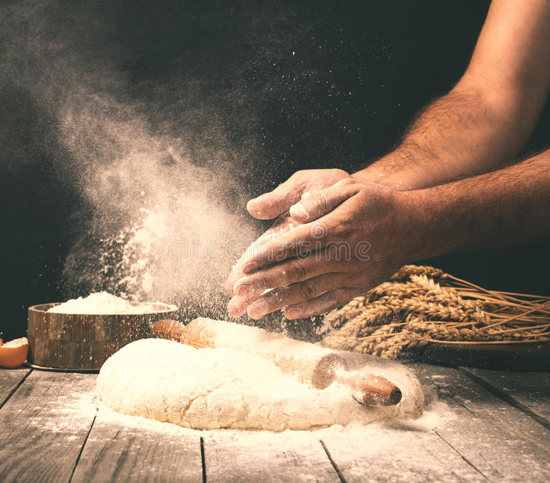 Man preparing bread dough on wooden table in a bakery. Close up royalty free stock photography
