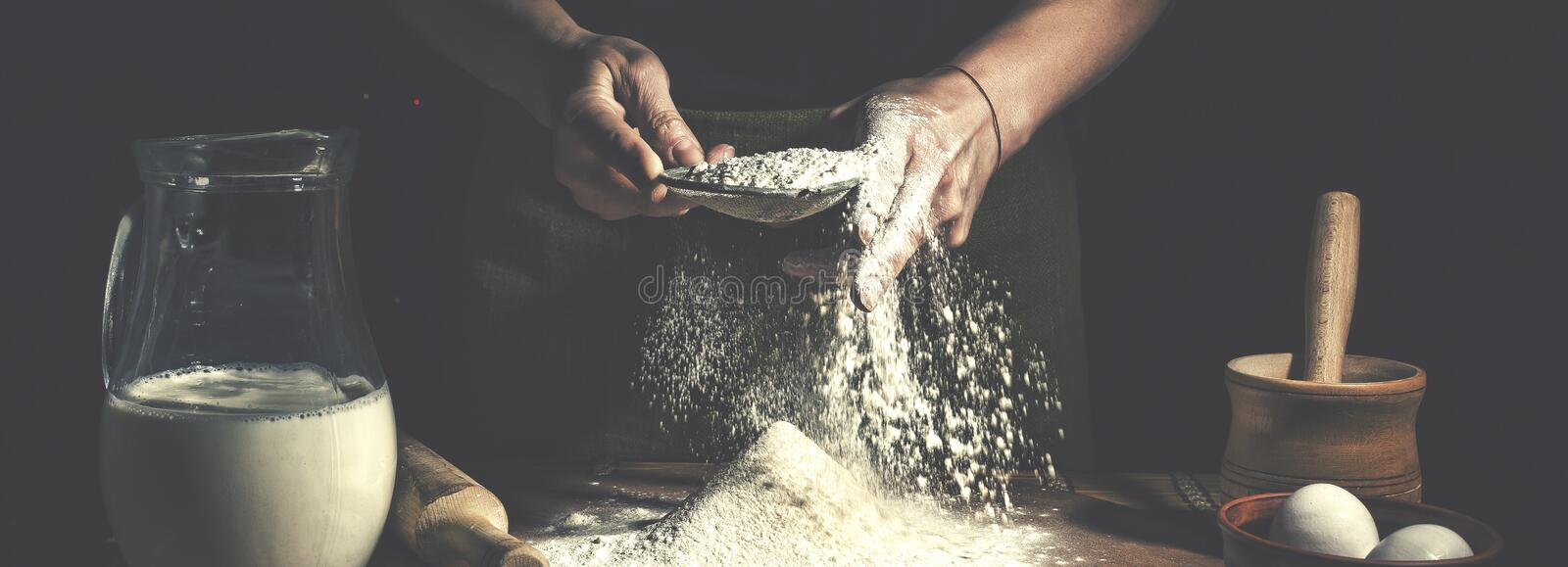 Man preparing bread dough on wooden table in a bakery close up. Preparation of Easter bread. royalty free stock photography