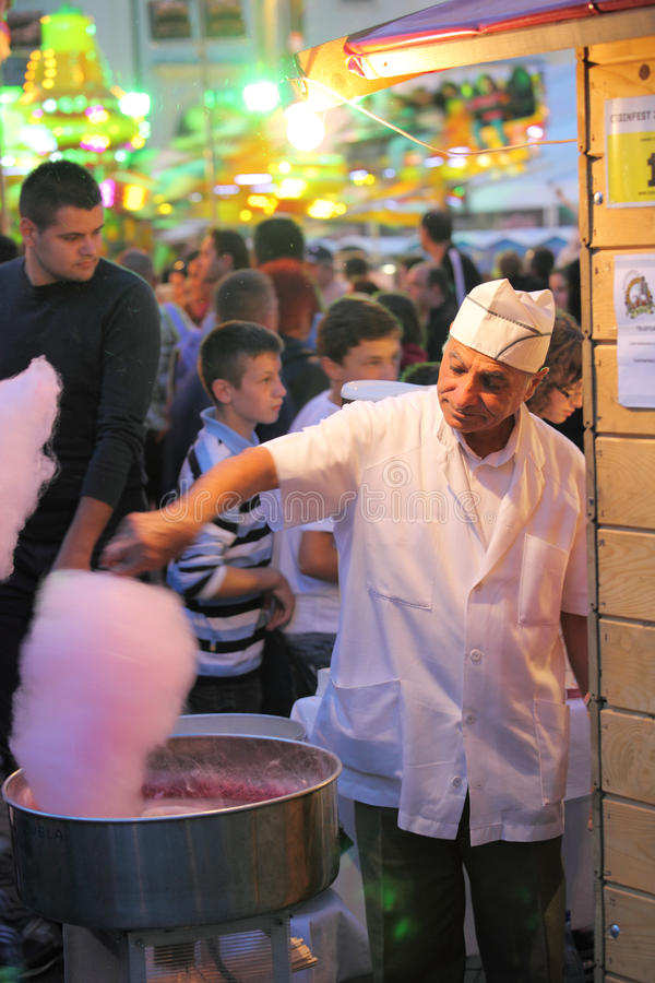 Man preparing cotton candy. Sibiu, Romania - September 28, 2012: Man with a chef hat on head preparing a cotton candy at CibinFest beer festival, the Romanian stock photography