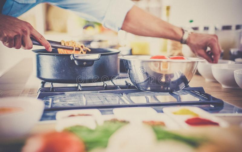 Man preparing delicious and healthy food in the home kitchen.  royalty free stock images