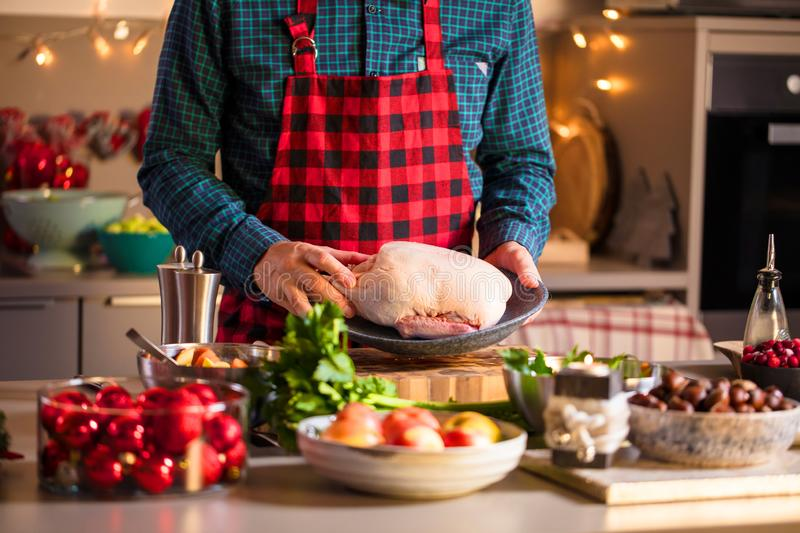 Man preparing delicious and healthy food in the home kitchen for christmas Christmas Duck or Goose. Man preparing delicious and healthy food in the home kitchen royalty free stock photos