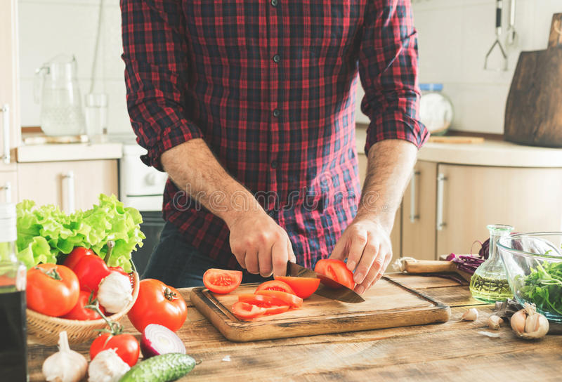 Man preparing delicious and healthy food in the home kitchen. On a sunny day royalty free stock images
