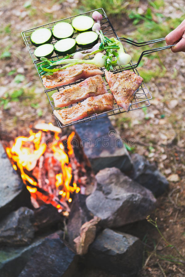 Man preparing dinner on campfire, adventure lifestyle camping vacation stock photo