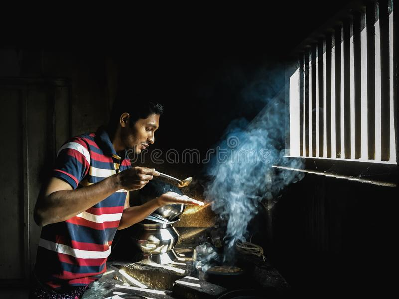 Man preparing the dishes for a festive dinner in a traditional kitchen in Kerala. stock image