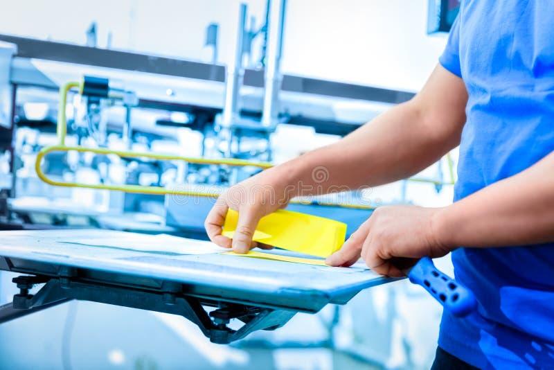 Man preparing fabric for screen printing. royalty free stock image