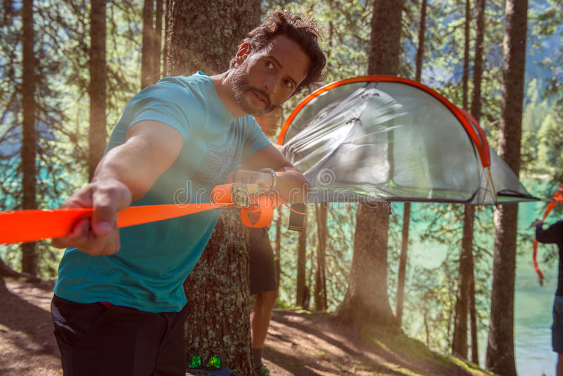 Man preparing hanging tent camping in forest woods during sunny day near lake.Group of friends people summer adventure. Journey in mountain nature outdoors stock photography