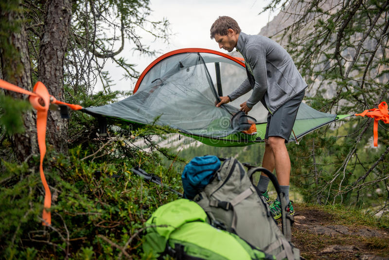 Man preparing hanging tent camping mosquito net in overcast day. Group of friends people summer adventure journey in. Mountain nature outdoors. Travel exploring royalty free stock image
