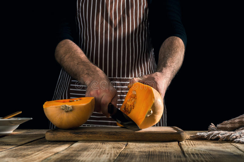 Man preparing healthy food from a pumpkin. On a wooden table royalty free stock images