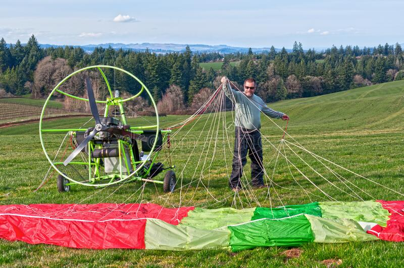 Preparing motorized paraglider for flight in sky. Man preparing his parachute on his motorized paraglider for an aerial adventure stock images