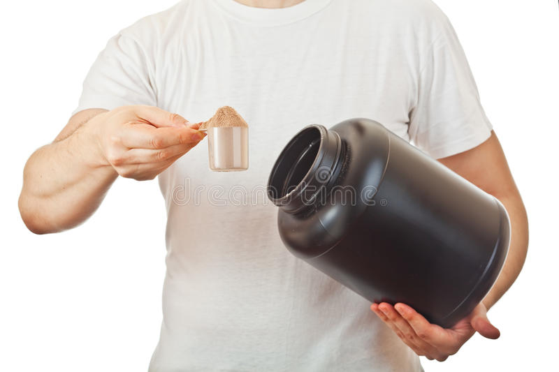 Man preparing his post workout protein shake. Taking a scoop of chocolate whey isolate powder from the black container, isolated on white royalty free stock images