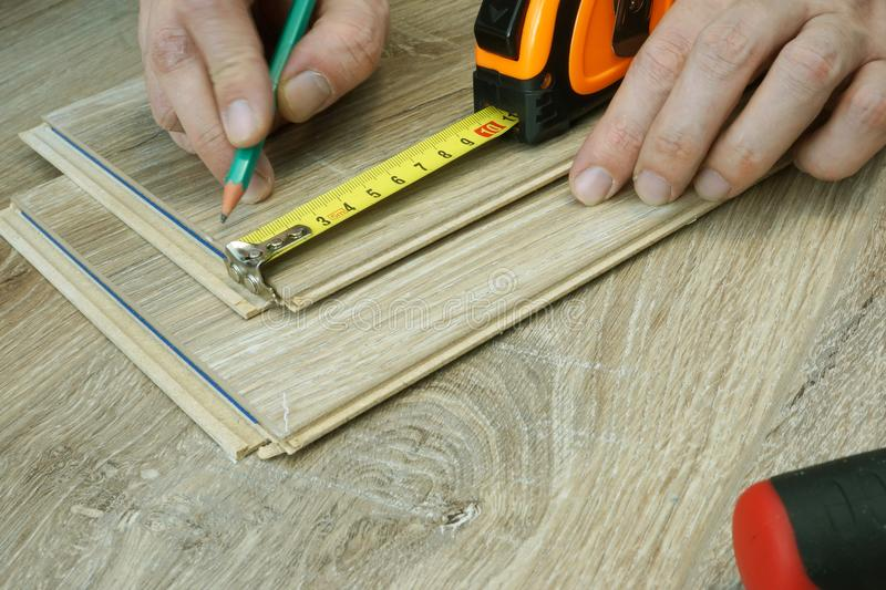 Man preparing for installation of laminate flooring. Renovation of floor. A Man is preparing for installation of laminate flooring. Renovation of floor royalty free stock images