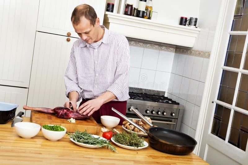 Download Man Preparing Meat In Kitchen Stock Photo - Image: 28483210