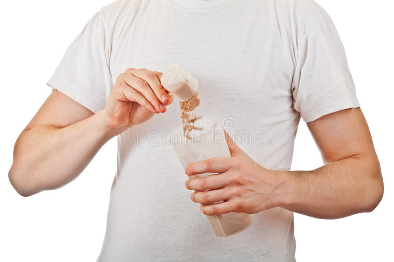 Man preparing post workout protein shake. Man preparing his post workout protein shake with a scoop of chocolate whey isolate powder in the shaker isolated on stock images