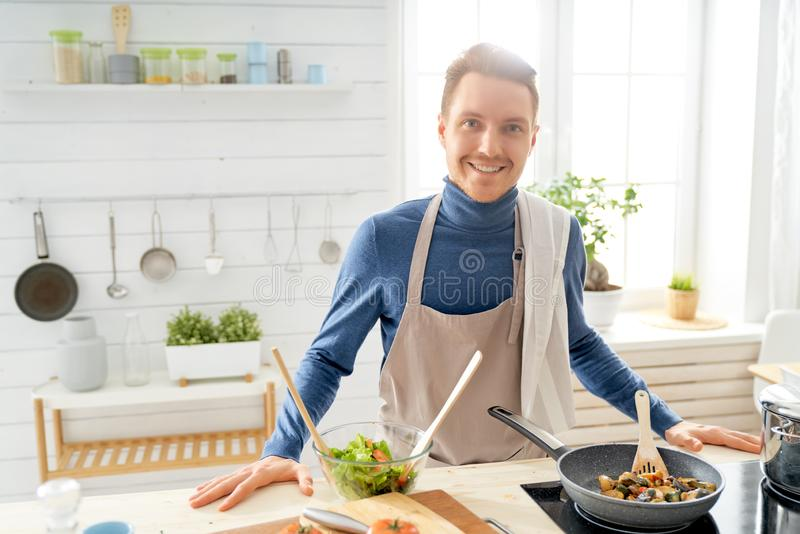 Man is preparing the proper meal. Healthy food at home. Happy man is preparing the proper meal in the kitchen royalty free stock image