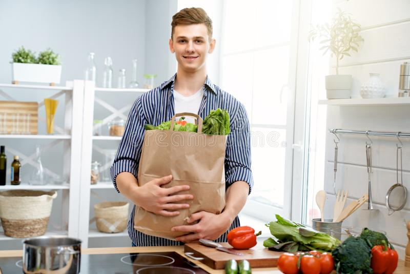 Man is preparing the proper meal. Healthy food at home. Happy man is preparing the proper meal in the kitchen stock photos