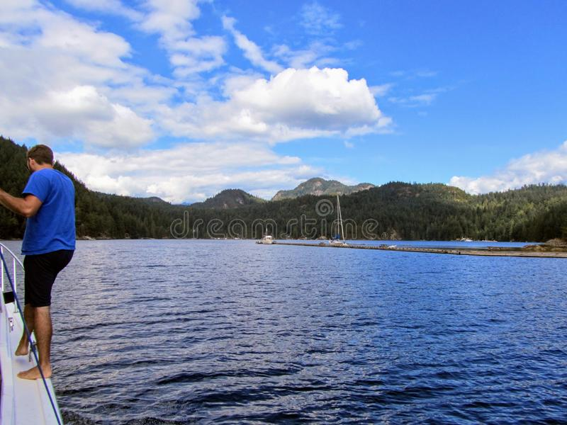 A man preparing to dock his boat at a dock on Alexander Island, on Gambier Island, in Howe Sound, British Columbia, Canada. A beautiful summer day with calm royalty free stock photography