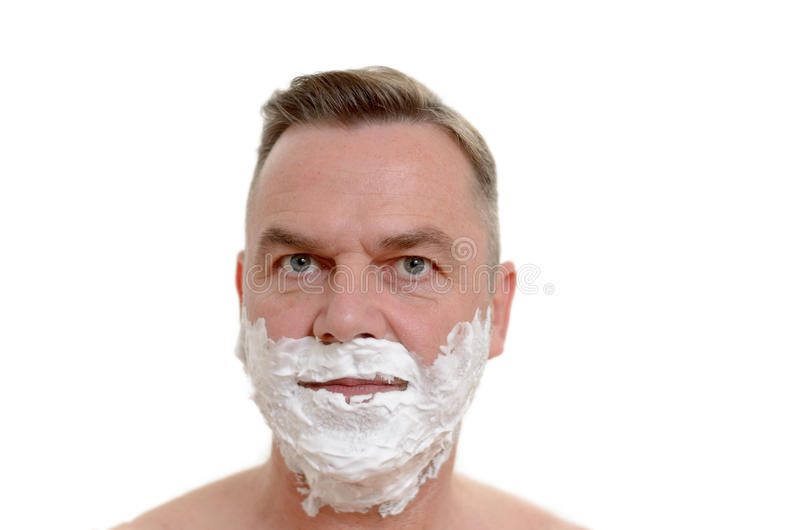 Man preparing to shave his beard. Standing with lathered white shaving cream covering his lower face, headshot on white stock photos