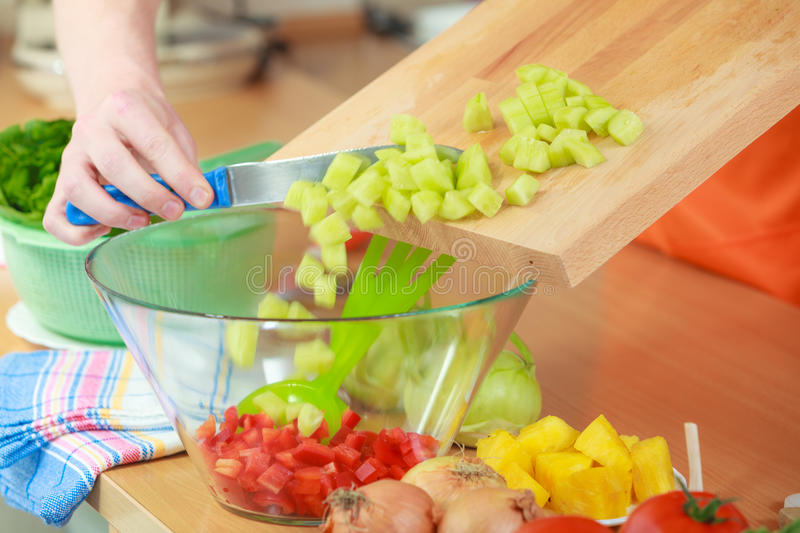 Man preparing vegetables salad slicing cucumber. Healthy eating, vegetarian food, cooking, dieting and people concept. Closeup man hands in kitchen at home royalty free stock image