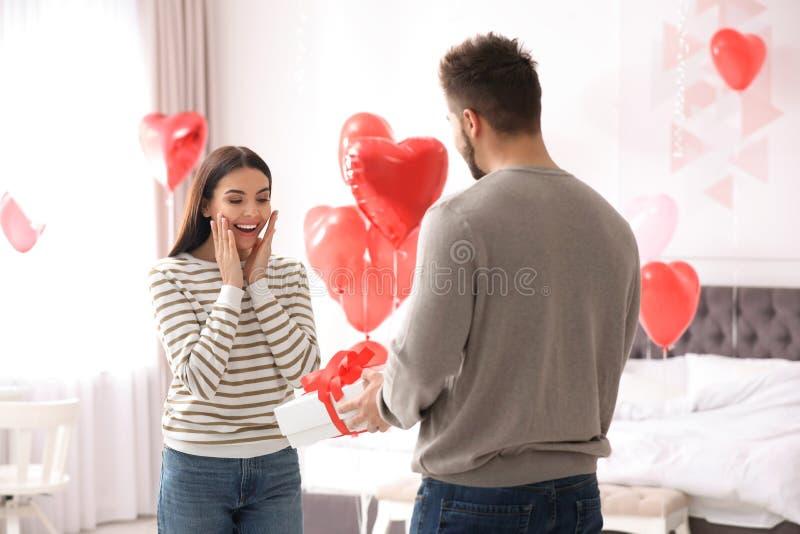 Man presenterar gåva till sin flickvän i sovrum med hjärtformade ballonger Alla hjärtans dag royaltyfria foton