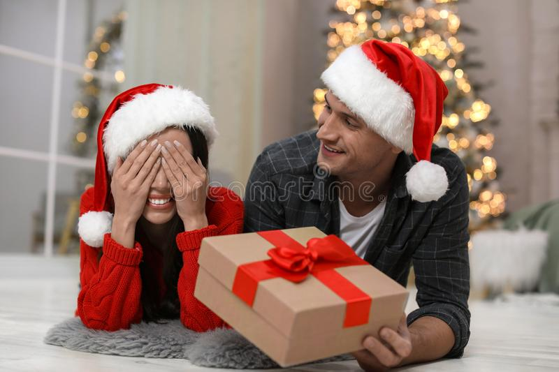 Man presenting Christmas gift to his girlfriend. At home royalty free stock photography