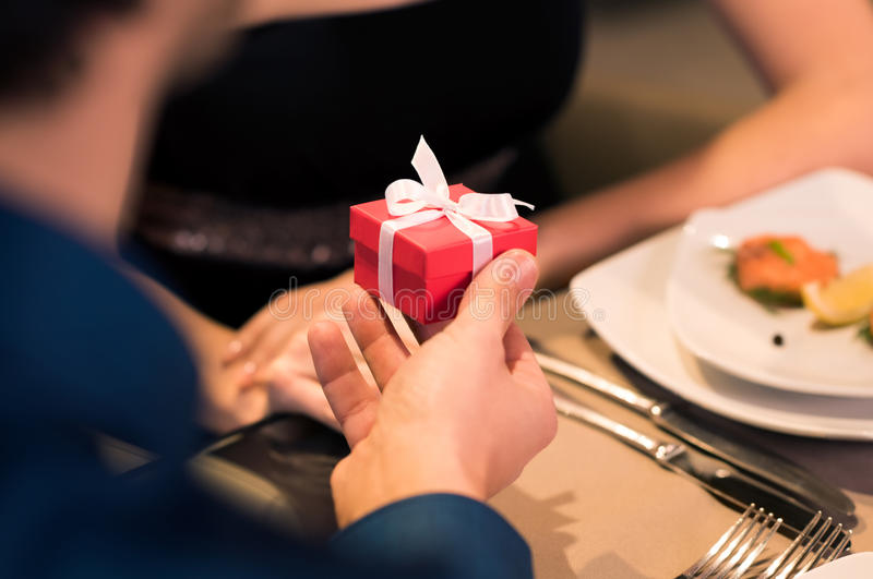 Man presenting a gift. Young men gifting a small red box to young woman. Husband give a present to wife on her birthday. Close up of boyfriend hand makes a stock photography