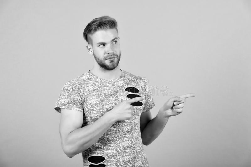 Man presenting product on grey background. Macho with bearded face point finger gesture. Presentation, advert. Advertisement and promotion concept, copy space stock photography