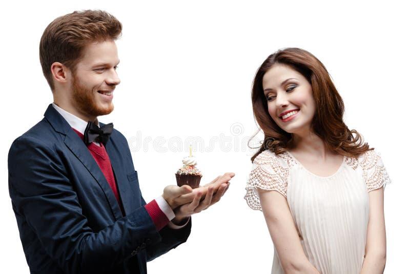Man presents birthday cake to his girlfriend. Isolated on white stock photo