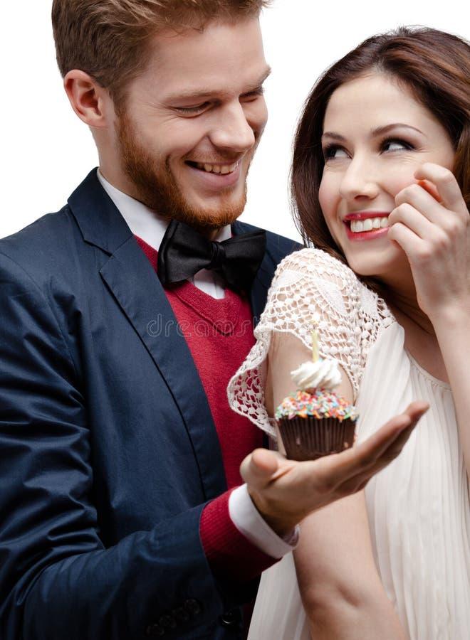 Man presents birthday cake to his girlfriend who likes it. Man presents birthday cake to his pretty girlfriend who likes it very much, isolated on white stock image