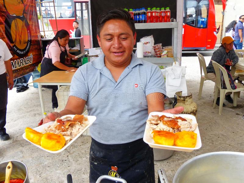 Man presents dishes with roasted pork, Ecuador stock images