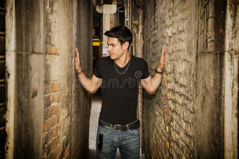 Man pressed between two walls. Concept of. Young man pressed between two walls. Concept of oppression, anxiety. Standing in Narrow Hallway of Decrepit Abandoned stock photo