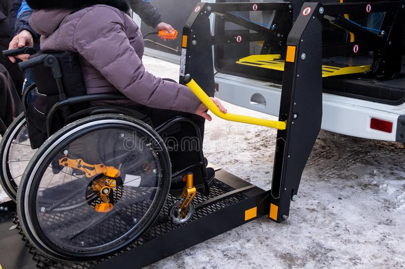 A man presses a button on the control panel to pick up a woman in a wheelchair in a taxi for the disabled. Black lift specialized stock photos