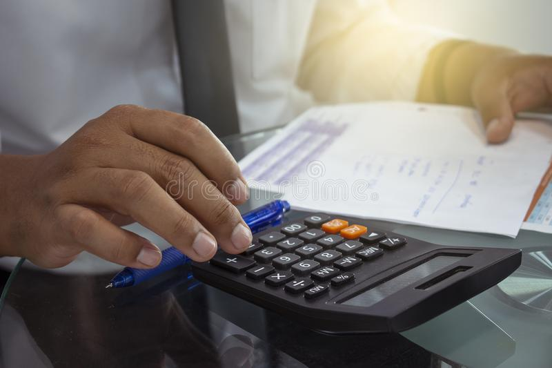 Man pressing calculator for business finance on car showroom blurry background.for automotive or transportation, adult. Young, male, vehicle, automobile royalty free stock photography