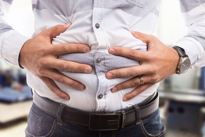 Man pressing bloated abdomen or belly as cramp flatulence problem. Man pressing grabbing bloated abdomen or belly as cramp flatulence constipation problem royalty free stock image