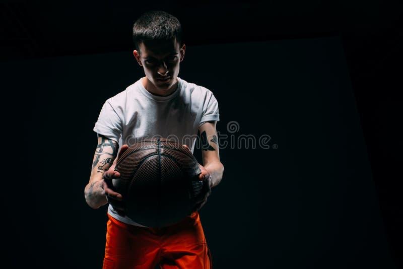 Man in prison uniform holding basketball ball. On dark background royalty free stock photos