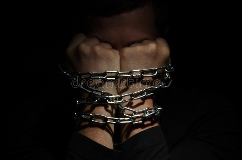A man prisoner chained in a chain clinging to his head against a black background royalty free stock image