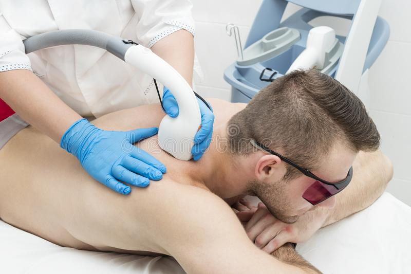 Man on the procedure of laser hair removal. In the beauty salon stock images