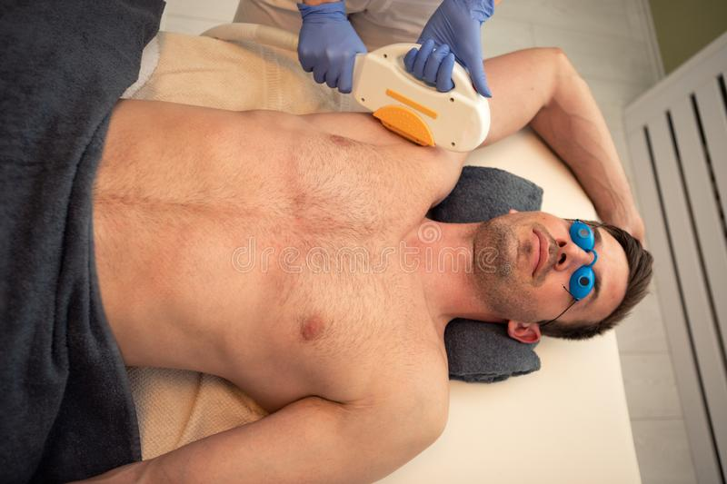 Man on the procedure of laser hair removal stock photography
