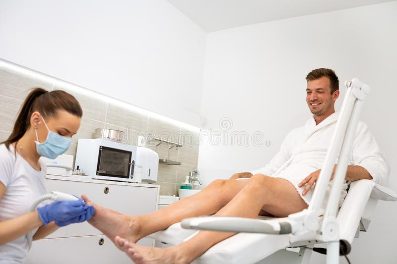 Man and the procedure of pedicure stock images